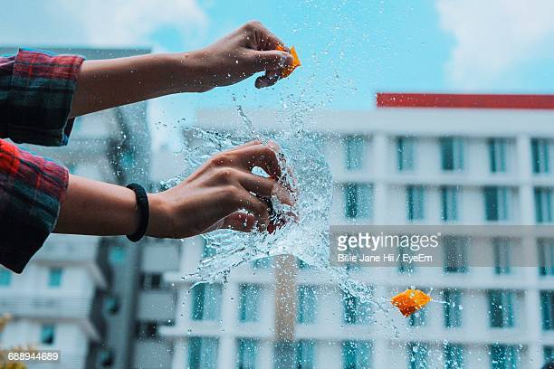 Cropped Image Of Woman Bursting Water Bomb