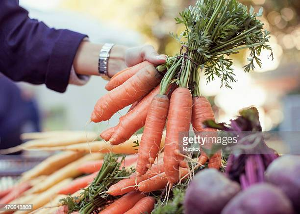 Cropped image of woman buying carrots at market stall