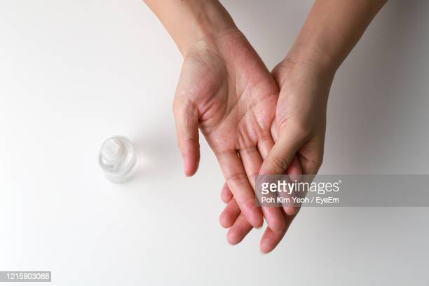 cropped image of woman cleaning hands with sanitizer over white background - hand sanitizer stockfoto's en -beelden