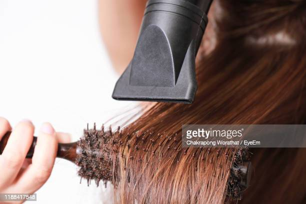 cropped image of woman combing hair with dryer against white background - capelli lisci foto e immagini stock