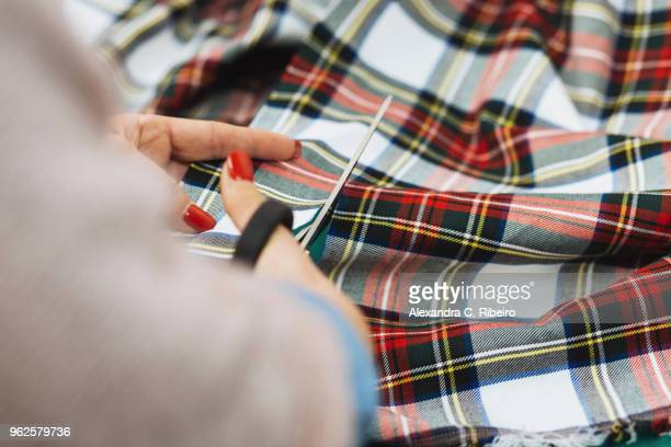 Cropped image of woman cutting plaid textile