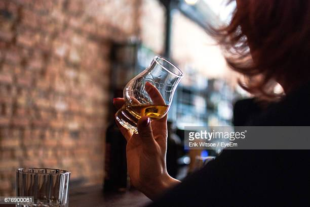 cropped image of woman drinking whiskey at table in bar - whisky stock photos and pictures