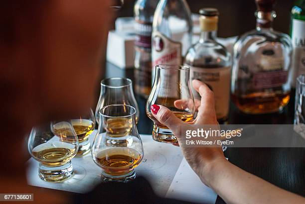 cropped image of woman drinking whiskey at table in bar - scotch whiskey stock pictures, royalty-free photos & images