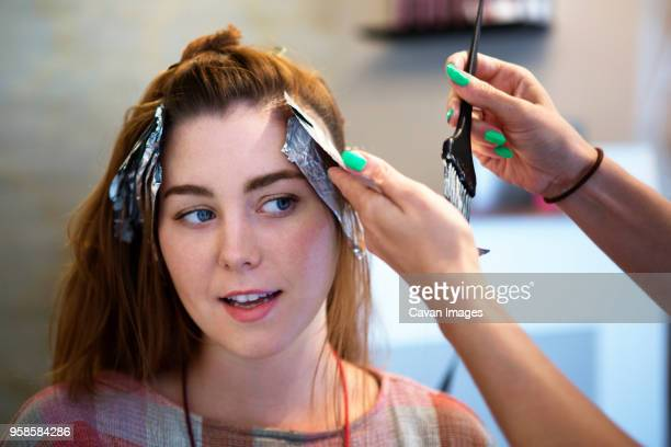 cropped image of woman dying customers hair in salon - cavan images foto e immagini stock
