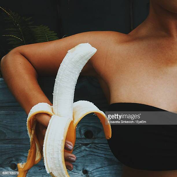 Cropped Image Of Woman Eating Banana While Sitting On Bench