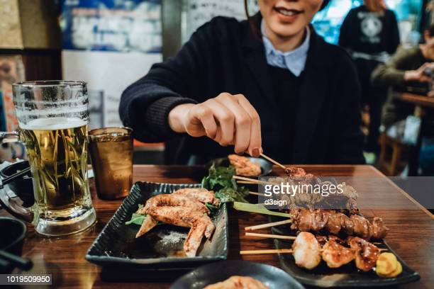 cropped image of woman enjoying traditional japanese yakitori and drinking beer in a japanese style restaurant - huhn geflügelfleisch stock-fotos und bilder