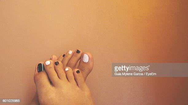 Cropped Image Of Woman Feet With Nail Polish Against Wall