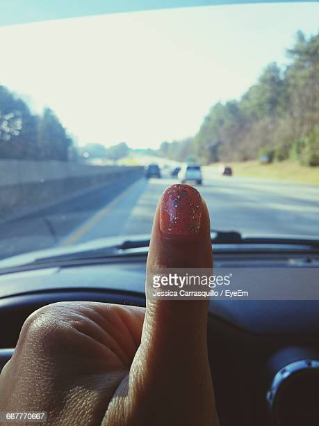 Cropped Image Of Woman Gesturing Thumbs Up In Car