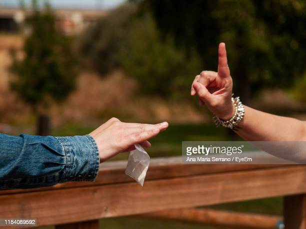 cropped image of woman gesturing to friend giving heroin packet - addiction stock pictures, royalty-free photos & images