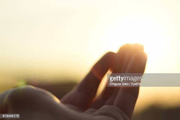 Cropped Image Of Woman Hand Against Sun Shining In Sky