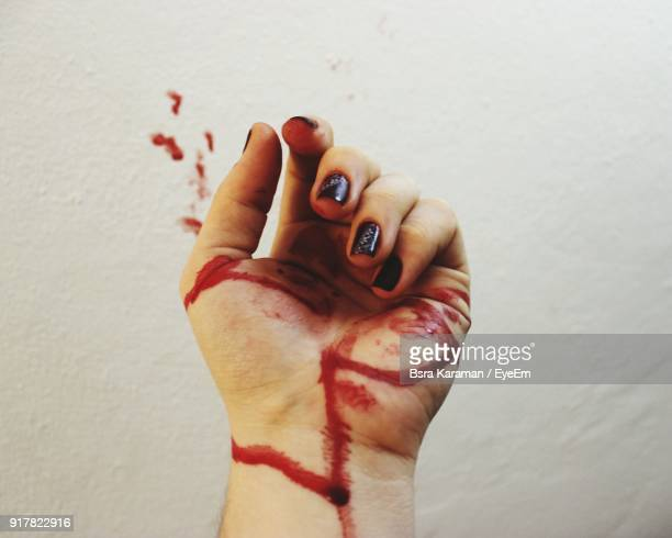 Cropped Image Of Woman Hand Covered With Blood Against Wall