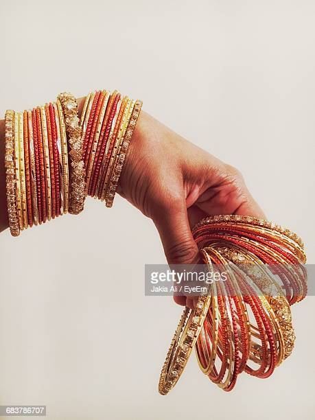 cropped image of woman hand holding bangles against white background - バングル ストックフォトと画像