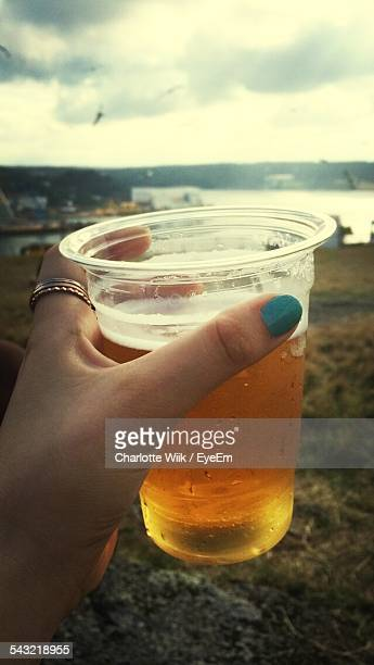 Cropped Image Of Woman Hand Holding Beer Glass On Beach
