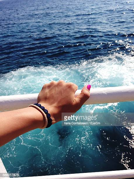 Cropped Image Of Woman Hand Holding Boat Railing In Sea