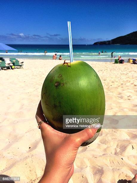 Cropped Image Of Woman Hand Holding Coconut At Beach