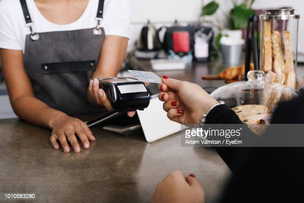 cropped image of woman hand holding credit card while making payment in cafe - contactless payment stock pictures, royalty-free photos & images