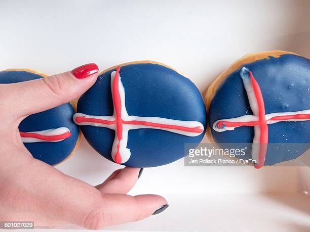 Cropped Image Of Woman Hand Holding Icelandic Flag Donuts