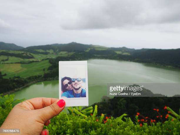 Cropped Image Of Woman Hand Holding Instant Print Transfer Against Lake