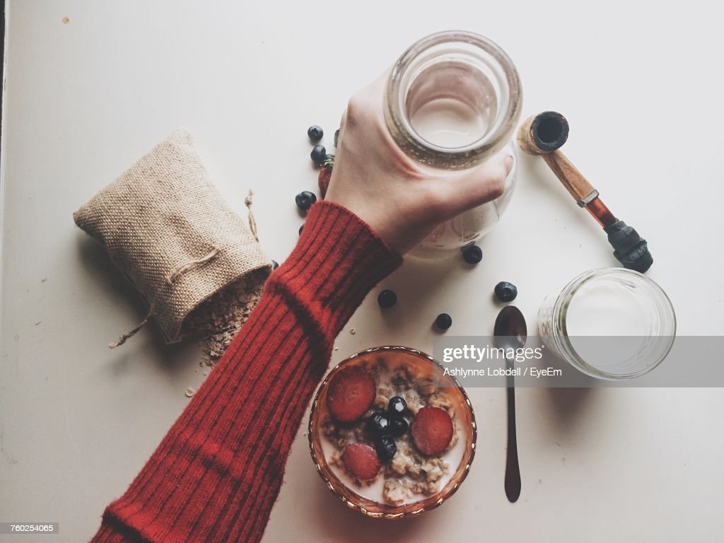 Cropped Image Of Woman Hand Holding Milk Jug With Breakfast On Table