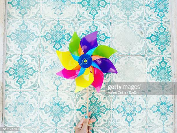 cropped image of woman hand holding pinwheel toy against patterned wall - paper windmill stock photos and pictures