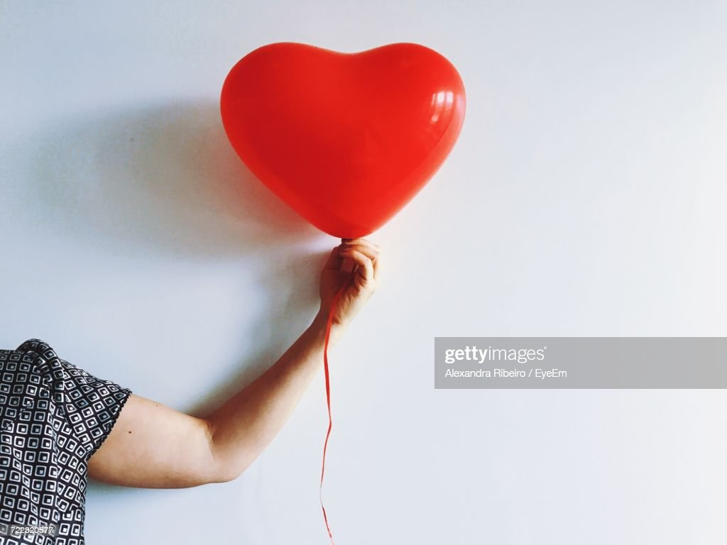 Cropped Image Of Woman Hand Holding Red Heart Shaped Balloon Against White Background : Stock Photo