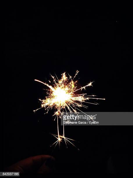 Cropped Image Of Woman Hand Holding Sparkler At Night