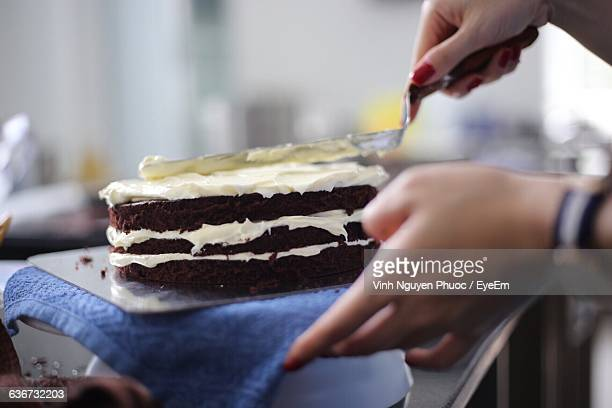 cropped image of woman hand icing cake in kitchen - decorating a cake stock pictures, royalty-free photos & images