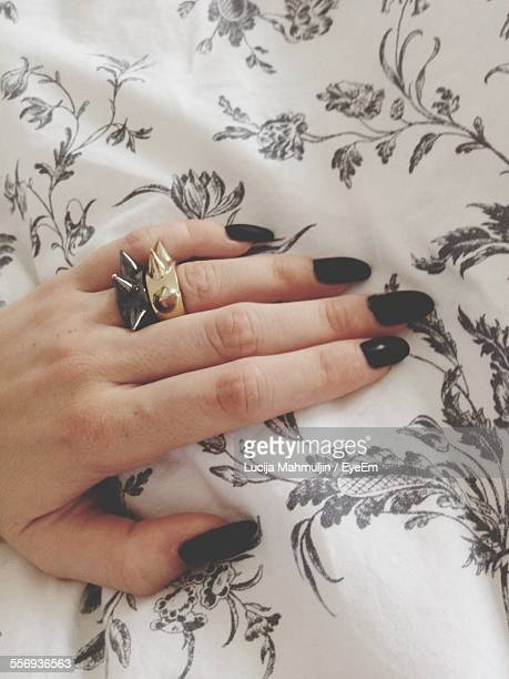 Cropped Image Of Woman Hand On Bed At Home