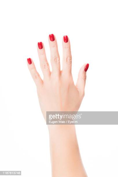cropped image of woman hand showing red nail polish against white background - red nail polish stock pictures, royalty-free photos & images