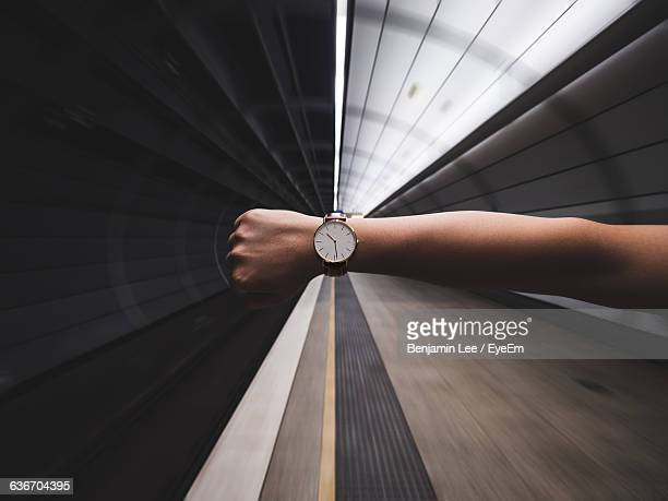 cropped image of woman hand showing wristwatch at subway station - istantanea foto e immagini stock
