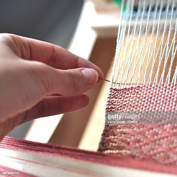 Cropped Image Of Woman Hand Weaving Thread