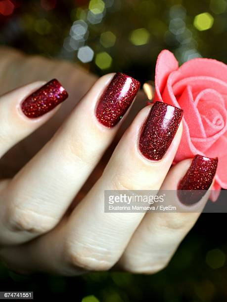 Cropped Image Of Woman Hand With Red Nail Polish Holding Artificial Rose
