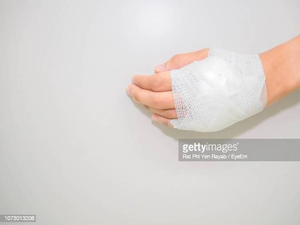 cropped image of woman hand wrapped with bandage against white background - primeros auxilios fotografías e imágenes de stock