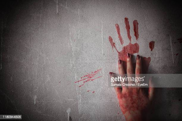 cropped image of woman hands with blood on wall - killing stock pictures, royalty-free photos & images