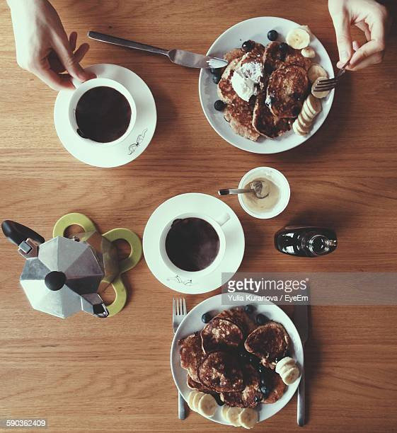 Cropped Image Of Woman Hands With Pie And Black Coffee On Table