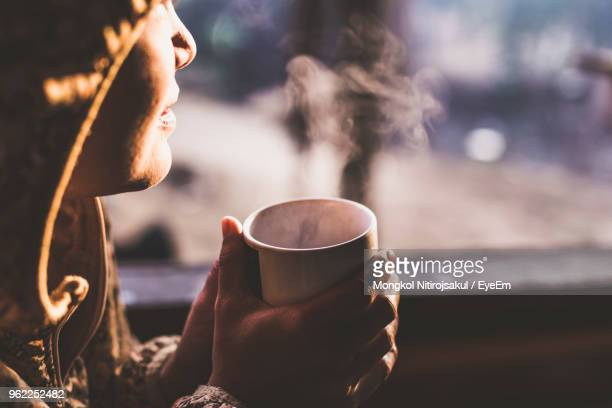 cropped image of woman having drink during sunset - coffee drink stock pictures, royalty-free photos & images