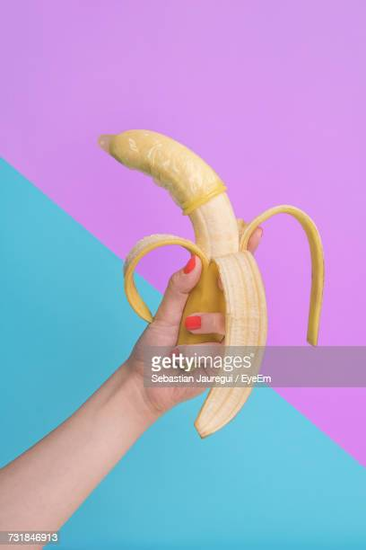 cropped image of woman holding banana with condom against blue and pink wall - foreskin stock pictures, royalty-free photos & images