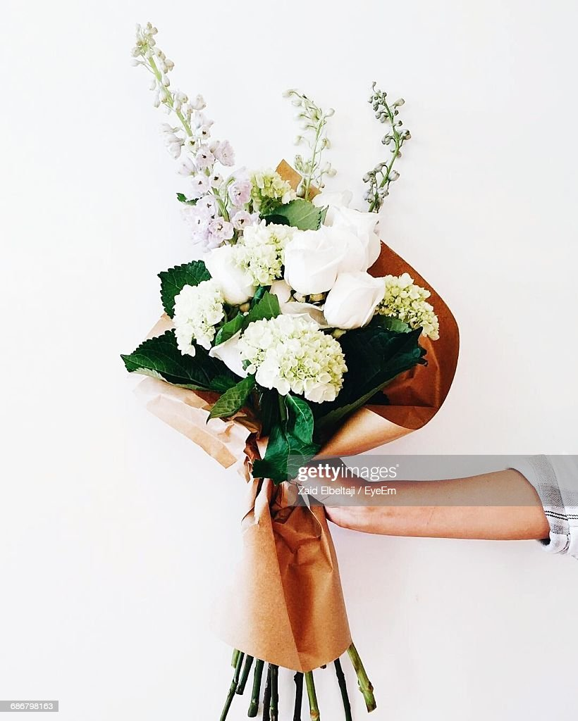 Cropped Image Of Woman Holding Bouquet Against White Background : Stock Photo