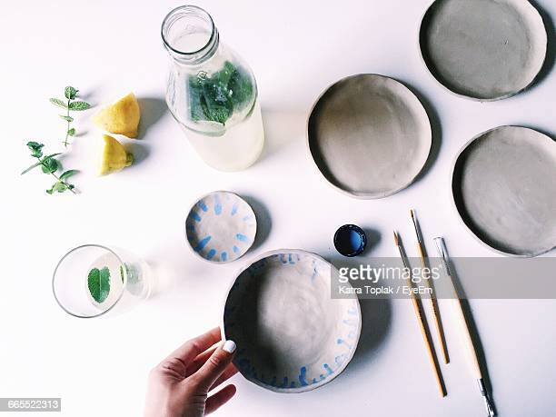 Cropped Image Of Woman Holding Bowl On Table At Home