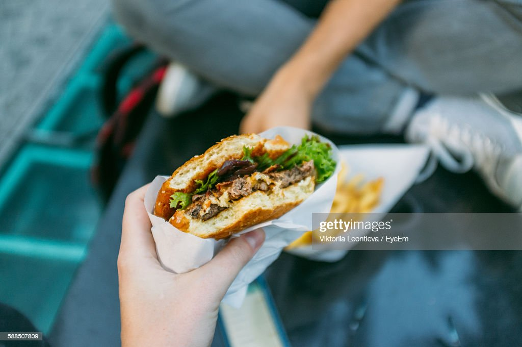 Cropped Image Of Woman Holding Burger : Stock-Foto