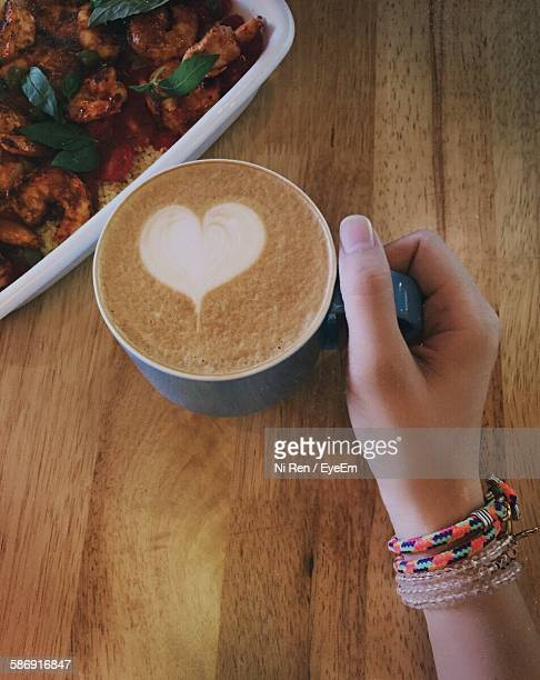 Cropped Image Of Woman Holding Cappuccino At Table