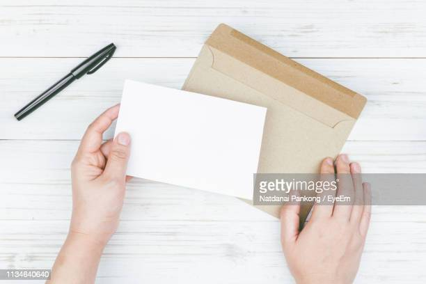 cropped image of woman holding card with envelop on table - greeting card bildbanksfoton och bilder