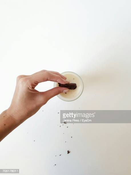 Cropped Image Of Woman Holding Chocolate Cookie In Milk On White Background