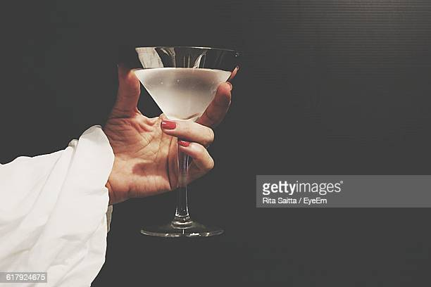 Cropped Image Of Woman Holding Cocktail Drink Against Black Background