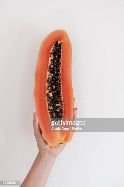 Cropped Image Of Woman Holding Halved Papaya Over White Background
