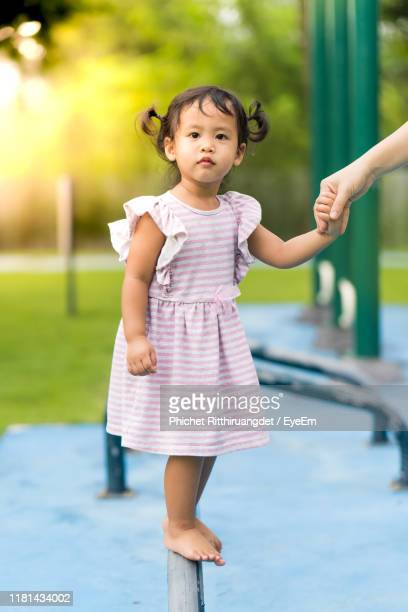 cropped image of woman holding hands with daughter standing on railing at playground - phichet ritthiruangdet stock photos and pictures