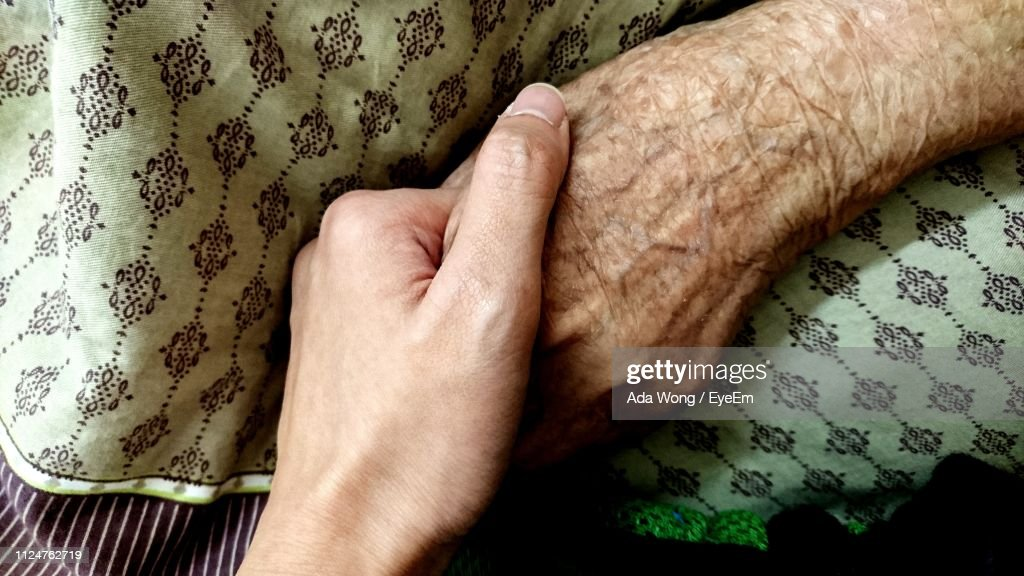 Cropped Image Of Woman Holding Hands With Mother : Stock Photo