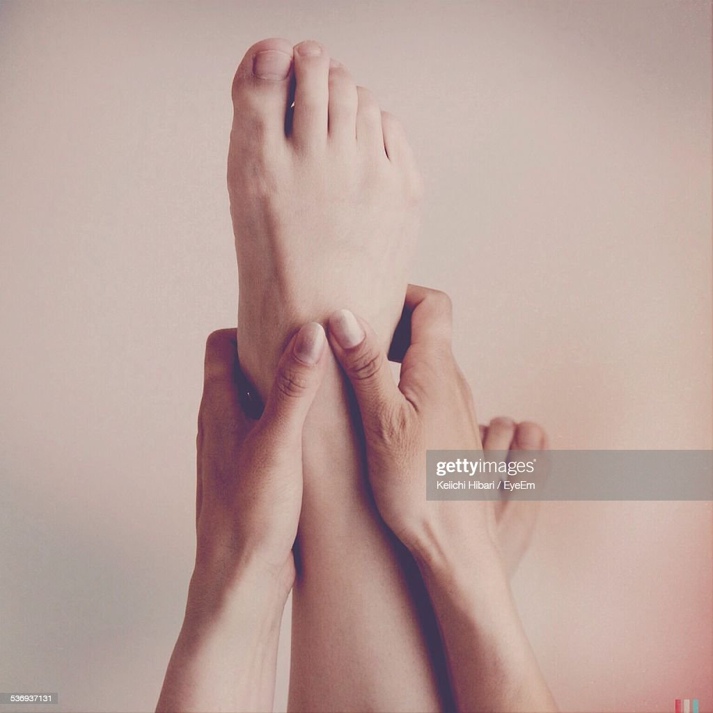 Cropped Image Of Woman Holding Leg Against Wall : Stock Photo