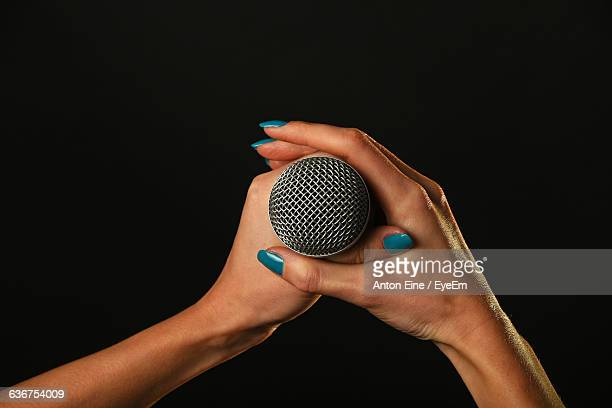 Cropped Image Of Woman Holding Microphone Against Black Background