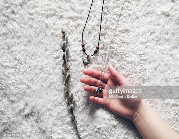 Cropped Image Of Woman Holding Necklace On Fur